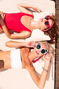 Onze vakantie. bovenaanzicht van mooie ontspannen modellen nemen ontslag op het strandbed