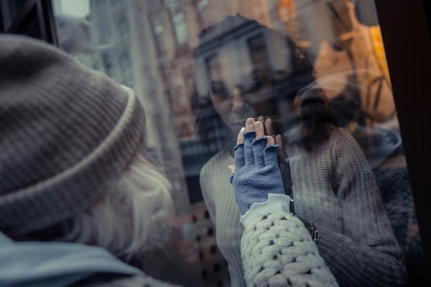 Onze verbinding. aardige, aangename vrouwen die hun handen naar het raam steken terwijl ze de verbinding tussen hen voelen