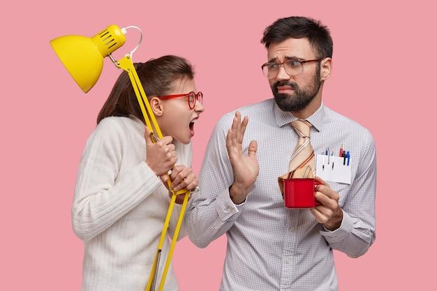 Onze verouderde, pissige vrouw houdt een gele lamp vast en roept naar luie groepgenoot, eist om hulp, draagt een bril. ontevreden man met baard hoort verwijten van vriendin