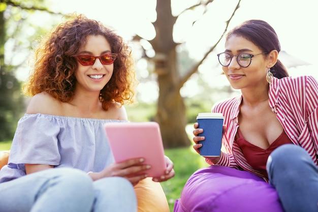 Onze vriendschap. opgetogen vrouw met krullend haar die een tablet vasthoudt en met haar vriend praat