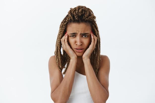 Onzeker en onrustig, verontrust zwart meisje dat in paniek raakt en er ongemakkelijk uitziet