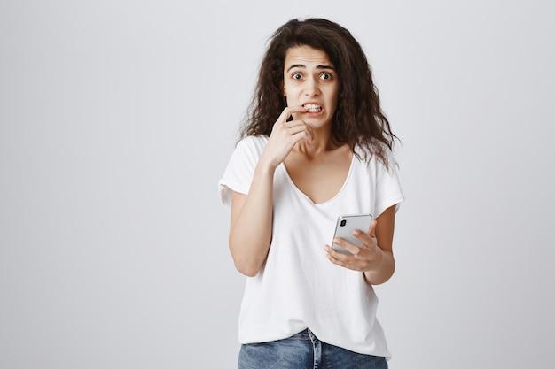 Onzeker en verlegen schattig meisje met behulp van mobiele telefoon, op zoek angstig