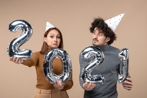 Onzeker jong koppel dragen nieuwe jaar hoed poses voor camera meisje en en man met en op grijs tonen