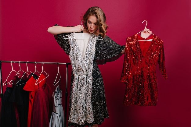 Onzeker jong vrouwelijk model met hangers met twee jurken, zich voorbereiden op feest