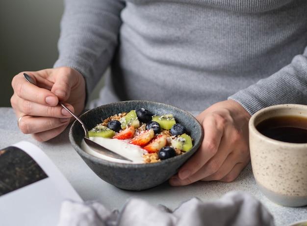 Onzeker meisje in grijze jurk aan de tafel met ontbijt. kom met yoghurt, muesli en bessen en kopje zwarte koffie en open magazine op grijze tafel