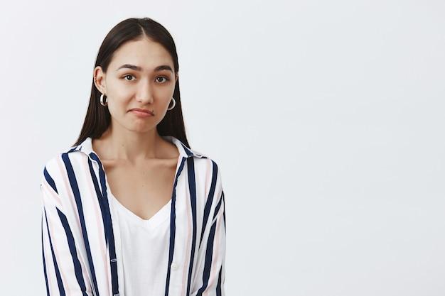 Onzekere aantrekkelijke en modieuze vrouw in gestreepte blouse, lip tuit en vragend starend, aarzelend en wil beleefd het aanbod afwijzen, ontevreden zijn