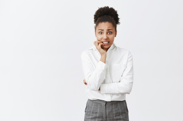 Onzekere bezorgde afro-amerikaanse vrouw die nagels bijt, heeft grote problemen