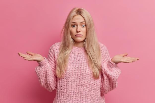 Onzekere blonde vrouw spreidt handpalmen en staat twijfelachtig binnenshuis kan geen keuze maken tussen twee opties draagt gebreide warme trui