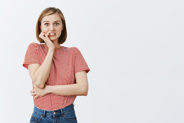 Onzekere en gealarmeerde jonge vrouw die vingernagel bijt en zich zorgen maakt