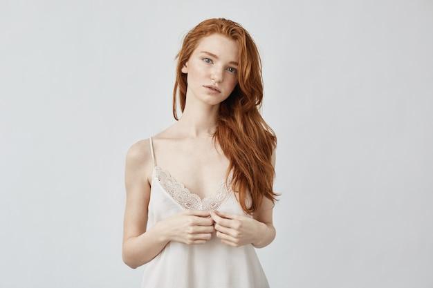 Onzekere jonge gember en sproeten in bodoir lingerie in de ochtend op witte muur.
