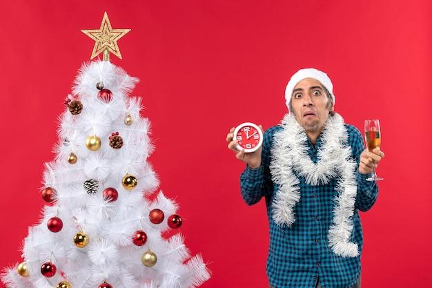 Onzekere jonge kerel met kerstman hoed en met een glas wijn en een klok in de buurt van de kerstboom
