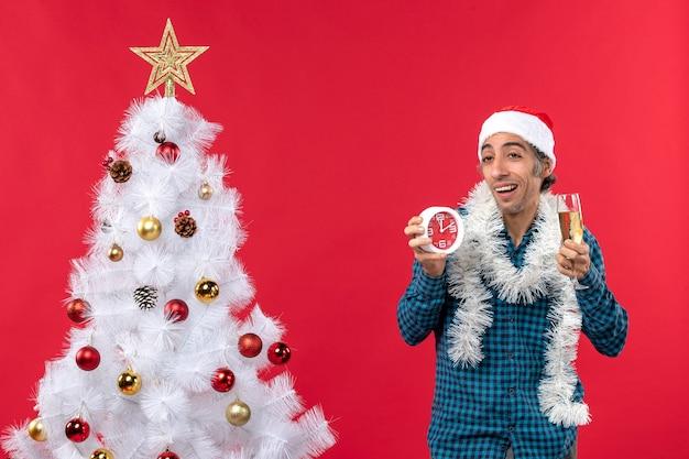 Onzekere jonge kerel met kerstman hoed en met een glas wijn en een klok staande in de buurt van de kerstboom op rood