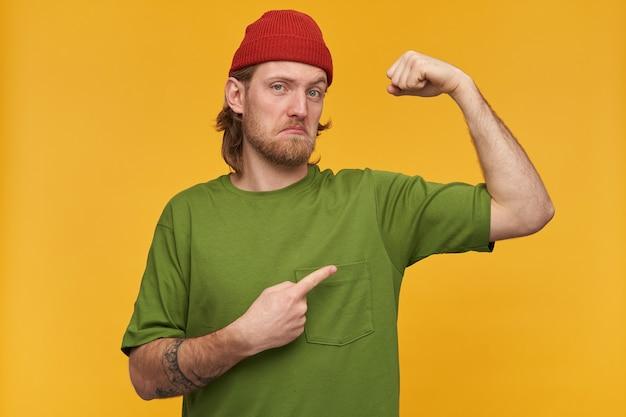 Onzekere mannelijke, knappe bebaarde man met blond haar. het dragen van een groen t-shirt en een rode muts. heeft tatoeages. wijzend met vinger en toont zijn biceps. geïsoleerd over gele muur