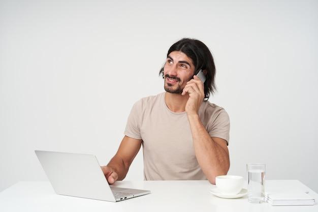 Onzekere mannelijke, knappe zakenman met zwart haar en baard. kantoor concept. zittend op de werkplek en telefoneren. kijken naar links op kopie ruimte, geïsoleerd op een witte muur