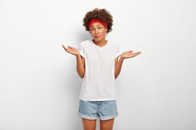 Onzekere, onwetende vrouw met afro-kapsel, spreidt haar handen uit met twijfel