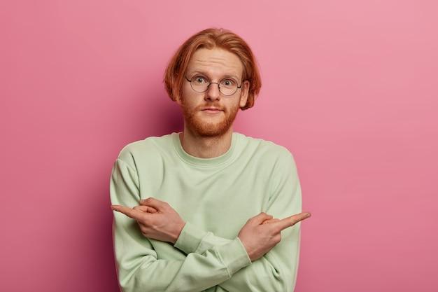 Onzekere roodharige man met baard wijst naar de linker- en rechterhoek