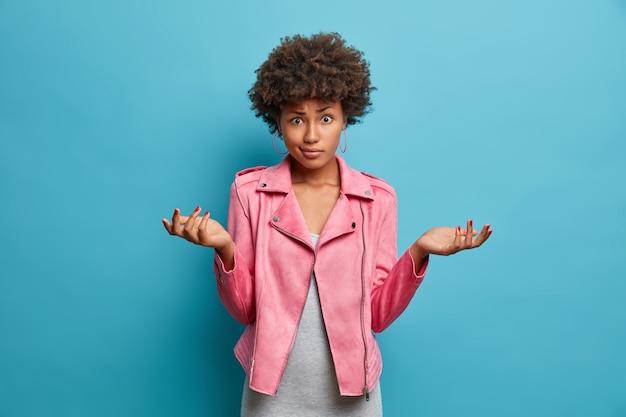 Onzekere twijfelachtige afro-amerikaanse vrouw met krullend haar spreidt handpalmen zijwaarts, gehinderd bij het maken van keuzes, gekleed in modieus roze jasje, staat onzorgvuldig, kan vragen niet beantwoorden, poseert binnen
