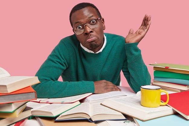 Onzekere verbaasde jonge man met donkere huid spreidt zijn handpalm in verbijstering, draagt een bril en trui, is nonchalant gekleed, heeft veel boeken op bureau