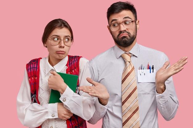 Onzekere verbaasde nerds kijken elkaar twijfelachtig aan