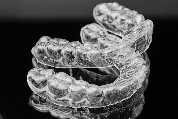 Onzichtbare transparante uitneembare beugel op de zwarte achtergrond. orthodontisch apparaat voor tandcorrectie. aligners voor het rechttrekken van tanden