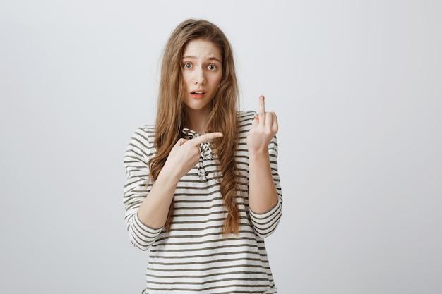 Onzorgvuldig onbeleefd meisje dat middelvinger toont bij persoon