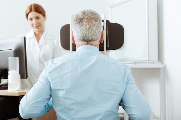 Oog analyse. grijsharige gepensioneerde man die zich goed voelt terwijl hij gezichtsanalyse krijgt in een privékliniek