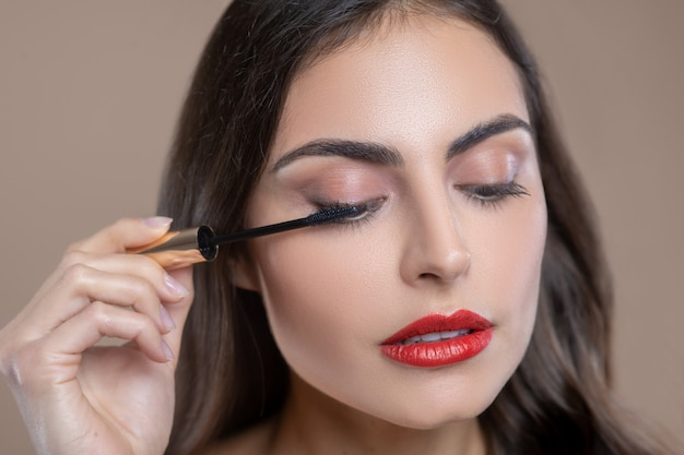 Oog cosmetica. gezicht van ernstige betrokken mooie vrouw met hangende oogleden met borstel met mascara in de buurt van haar oog