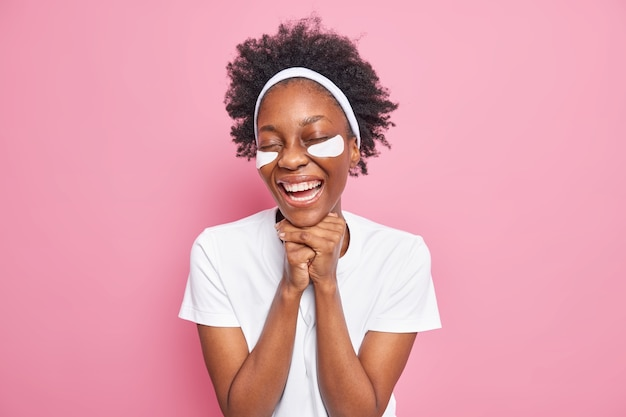 Oog huidverzorging. vrolijke jonge afro-amerikaanse vrouw houdt handen onder de kin glimlacht in grote lijnen brengt collageenpleisters aan voor het verwijderen van fijne lijntjes