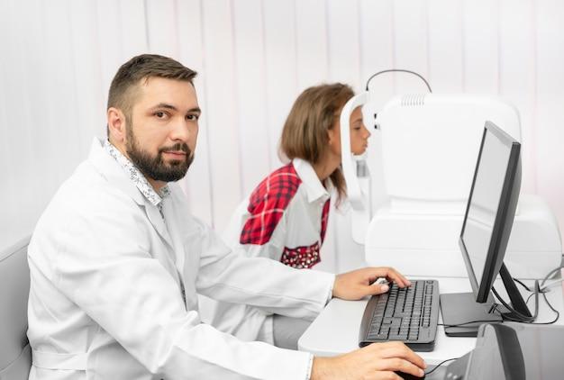 Oogarts die de ogen van de patiënt met speciale apparatuur onderzoekt