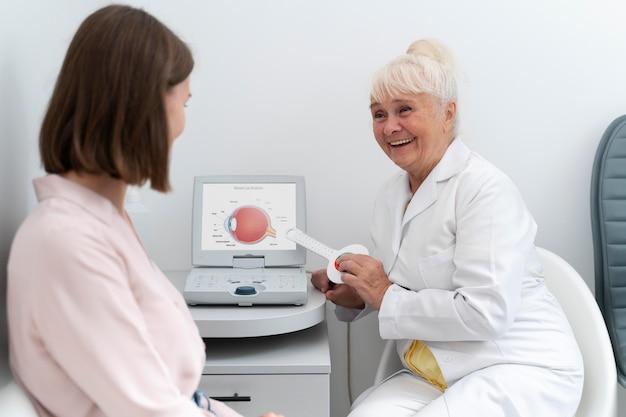 Oogarts die een patiënt in haar kliniek controleert