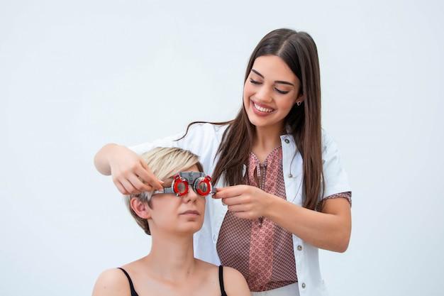 Oogarts die vrouw met optometrist proefkader onderzoekt