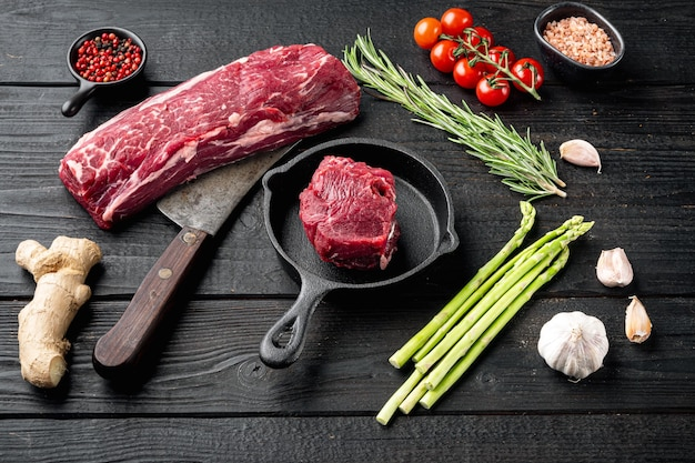 Oogfilet rundvlees gemarmerd vers vlees steak set, op gietijzeren koekenpan, op zwarte houten tafel