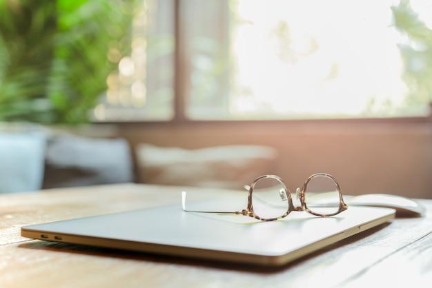Oogglazen bovenop laptop op bedrijfswerkplaats op onduidelijk beeldachtergrond.