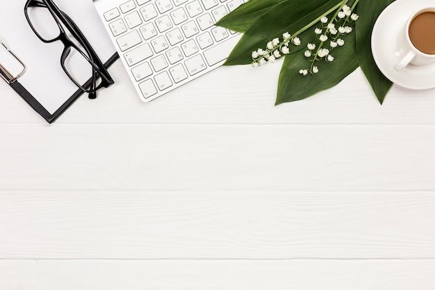 Oogglazen, klembord, toetsenbord, bloem en bladeren met koffiekopje op bureau