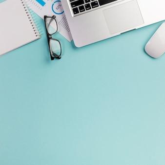 Oogglazen, laptop, muis en spiraalvormige blocnote op bureau