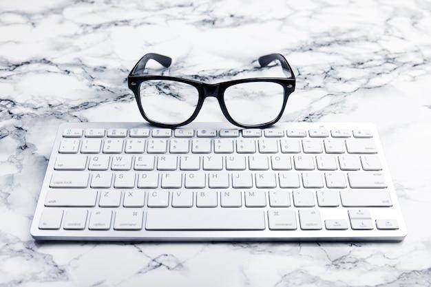 Oogglazen op een bureau of bureauscène met toetsenbord