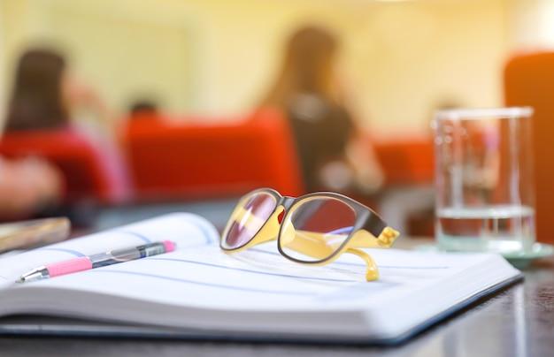 Oogglazen op het boek terwijl vergadering.