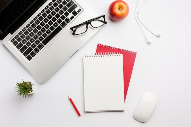 Oogglazen op laptop, appel, oortelefoons, kleurpotlood, spiraalvormige blocnote en muis op wit bureau