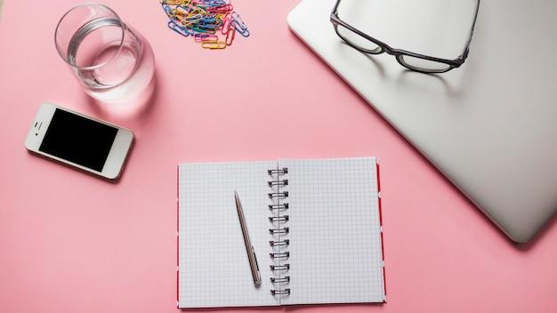 Oogglazen op laptop met kantoorbehoeften; smartphone en een glas water op roze achtergrond