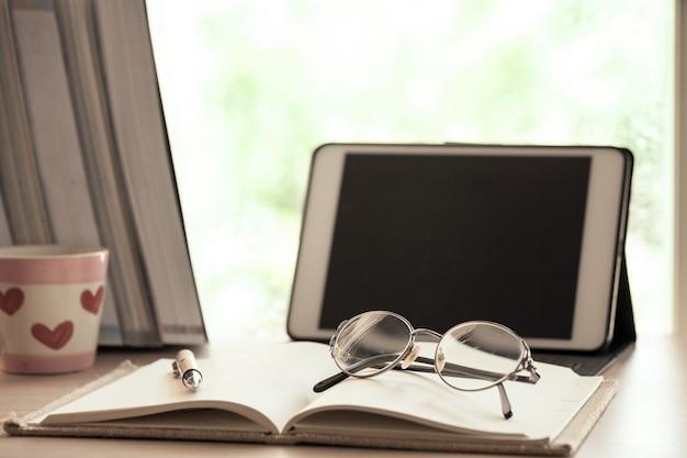 Oogglazen op notitieboekje met digitale tablet op het werk op regenachtige dag