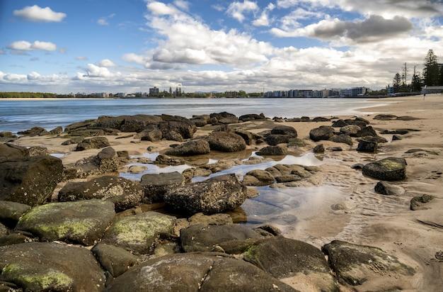 Ooghoogte shot van stenen in een strand onder de blauwe bewolkte hemel