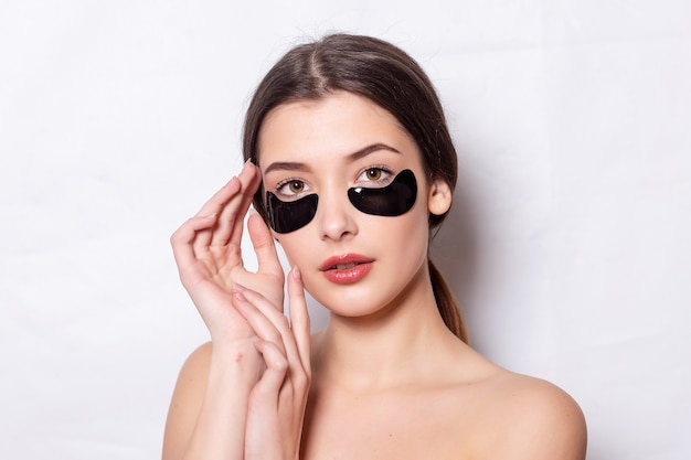 Ooglapje, mooie vrouw met natuurlijke make-up en zwarte hydrogel ooglapjes op de gezichtshuid. blanke vrouw gebruikt zwarte vlekken na het douchen, huidverzorging