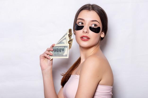 Ooglapje, mooie vrouw met natuurlijke make-up en zwarte hydrogel ooglapjes op de gezichtshuid. een jong bloggermeisje houdt proppen geld vast