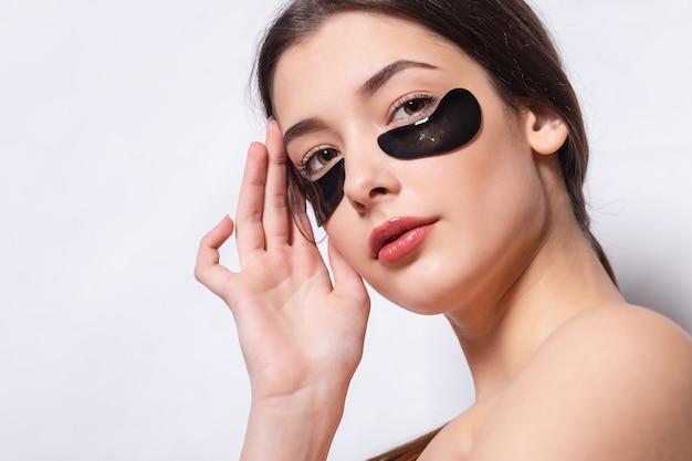 Ooglapje, mooie vrouw met natuurlijke make-up en zwarte hydrogel ooglapjes op de gezichtshuid.