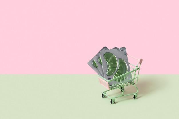 Ooglapjes in winkelwagen op groene achtergrondkleur gezichtsverzorging schoonheidsbehandeling concept