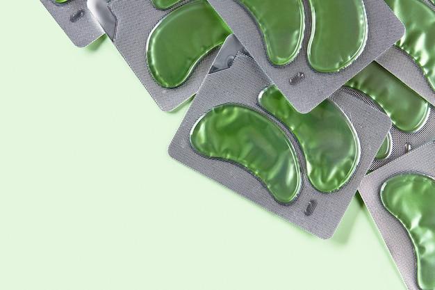 Ooglapjes over groene achtergrondkleur gezichtsverzorging schoonheidsbehandeling concept