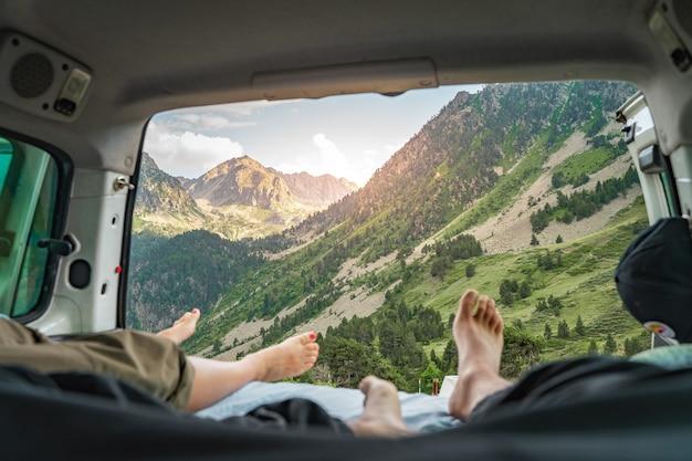 Oogpunt van de benen van een romantisch stel in een oud busje dat samen geniet van het geweldige landschap