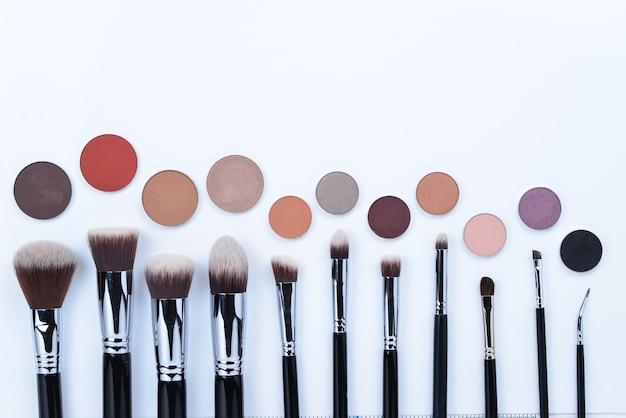 Oogschaduw en penselen voor make-up geïsoleerd op een witte achtergrond