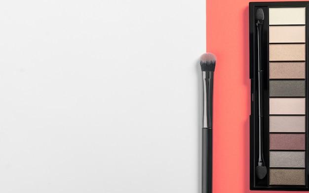 Oogschaduw poeder palet en penseel op koraal kleur achtergrond met kopie ruimte