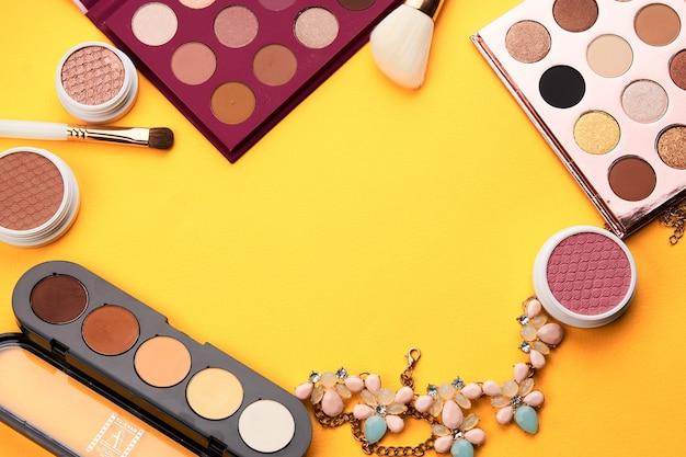 Oogschaduw professionele cosmetica blozen poeder gele achtergrond bovenaanzicht.